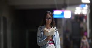 Muchacha que lee un libro en el subterráneo en el medio de la muchedumbre metrajes