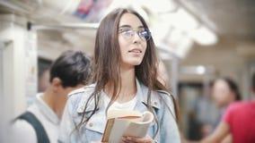 Muchacha que lee un libro en el subterráneo y que mira detrás la gente metrajes