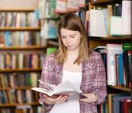 Muchacha que lee un libro en la biblioteca Fotos de archivo