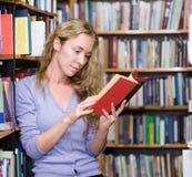 Muchacha que lee un libro en la biblioteca Fotografía de archivo