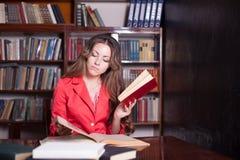 Muchacha que lee un libro en la biblioteca Foto de archivo