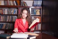 Muchacha que lee un libro en la biblioteca Fotografía de archivo libre de regalías