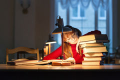 Muchacha que lee un libro en la biblioteca debajo de la lámpara Fotografía de archivo