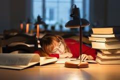 Muchacha que lee un libro en la biblioteca debajo de la lámpara Foto de archivo libre de regalías