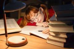 Muchacha que lee un libro en la biblioteca debajo de la lámpara Imagen de archivo