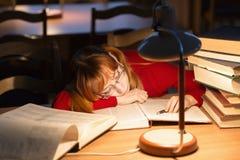 Muchacha que lee un libro en la biblioteca debajo de la lámpara Foto de archivo
