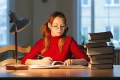 Muchacha que lee un libro en la biblioteca debajo de la lámpara Imagenes de archivo