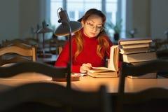 Muchacha que lee un libro en la biblioteca debajo de la lámpara Fotografía de archivo libre de regalías