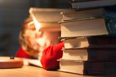 Muchacha que lee un libro en la biblioteca debajo de la lámpara Imágenes de archivo libres de regalías