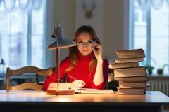 Muchacha que lee un libro en la biblioteca debajo de la lámpara Imagen de archivo libre de regalías