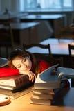 Muchacha que lee un libro en la biblioteca debajo de la lámpara Fotos de archivo