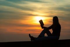 Muchacha que lee un libro en la pared en la puesta del sol Foto de archivo libre de regalías