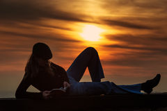 Muchacha que lee un libro en la pared en la puesta del sol Imagen de archivo