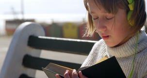 Muchacha que lee un libro en la playa 4k almacen de metraje de vídeo