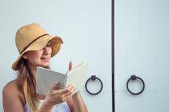 Muchacha que lee un libro en la puerta Imagen de archivo libre de regalías
