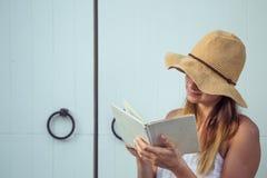 Muchacha que lee un libro en la puerta Imagen de archivo