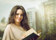 Muchacha que lee un libro en parque Imagenes de archivo