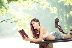 Muchacha que lee un libro en parque Fotografía de archivo