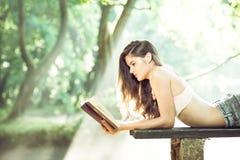 Muchacha que lee un libro en parque Foto de archivo libre de regalías