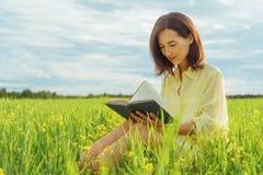 Muchacha que lee un libro en prado del verano Imagenes de archivo