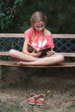 Muchacha que lee un libro en un banco en el parque Fotos de archivo