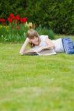 Muchacha que lee un libro en un jardín Imagen de archivo