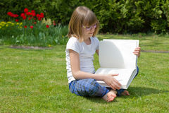 Muchacha que lee un libro en un jardín Imagen de archivo libre de regalías