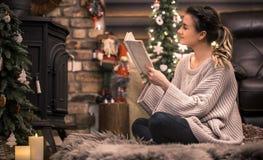 Muchacha que lee un libro en una atmósfera casera acogedora cerca de la chimenea foto de archivo libre de regalías
