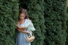 Muchacha que lee un libro en una cerca verde Fotografía de archivo