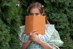 Muchacha que lee un libro en una cerca verde Fotos de archivo libres de regalías