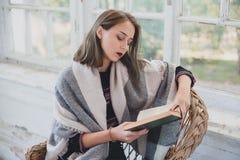 Muchacha que lee un libro en una silla de mimbre Fotografía de archivo