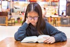 Muchacha que lee un libro en una tabla dentro de un lugar público con el blurre Fotos de archivo