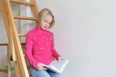 Muchacha que lee un libro mientras que se sienta en las escaleras de madera en el apartamento Imagenes de archivo