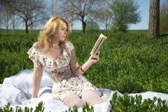 Muchacha que lee un libro que se sienta en la hierba Imagen de archivo