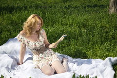 Muchacha que lee un libro que se sienta en la hierba Foto de archivo