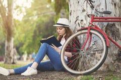 Muchacha que lee un libro que se inclina contra un árbol Fotos de archivo
