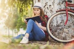 Muchacha que lee un libro que se inclina contra un árbol Foto de archivo libre de regalías