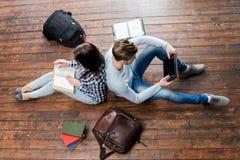 Muchacha que lee un libro y a un muchacho que usa una tableta Imagen de archivo