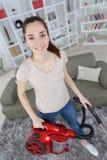 Muchacha que limpia la alfombra con la aspiradora foto de archivo libre de regalías