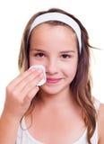Muchacha que limpia su cara con el cojín de algodón Fotos de archivo