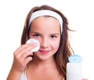 Muchacha que limpia su cara con la loción tónica Imágenes de archivo libres de regalías