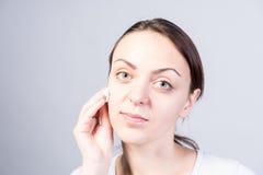 Muchacha que limpia su cara usando algodón con la despedregadora imágenes de archivo libres de regalías