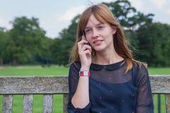 Muchacha que llama por teléfono con el teléfono móvil en naturaleza Fotografía de archivo