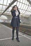 Muchacha que llama por teléfono en la estación de tren Imagenes de archivo