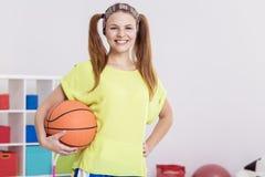 Muchacha que lleva a cabo baloncesto Imagen de archivo libre de regalías
