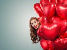Muchacha que lleva a cabo corazones de los globos Mujer sorprendida en el fondo blanco Sorpresa, tarjetas del día de San Valentín fotografía de archivo libre de regalías
