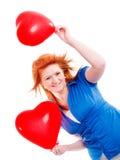 Muchacha que lleva a cabo dos corazones del globo de la tarjeta del día de San Valentín Imagenes de archivo