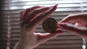 Muchacha que lleva a cabo el bitcoin del oro en su mano, ella el ` s gira una moneda brillante en el sol metrajes