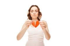 Muchacha que lleva a cabo el corazón rojo de papel roto de la tarjeta del día de San Valentín Foto de archivo libre de regalías