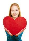 Muchacha que lleva a cabo el corazón rojo para el día de tarjeta del día de San Valentín Fotos de archivo libres de regalías